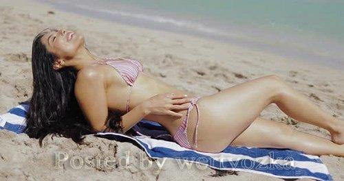 Beautiful Fit Girl in Bikini Sitting on Sand